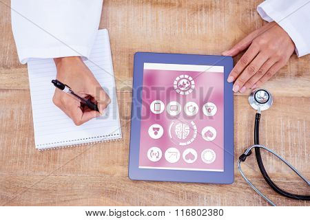 Medical app against doctor writing on a notepad