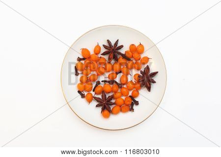 Frozen sea buckthorn, cloves, star anise, black pepper on a white saucer on a white background