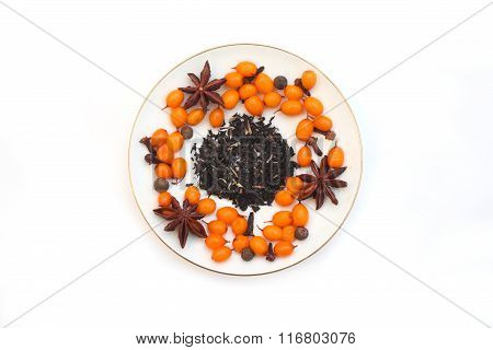 Frozen sea buckthorn, cloves, star anise, black pepper, tea leaves on a white saucer on a white back