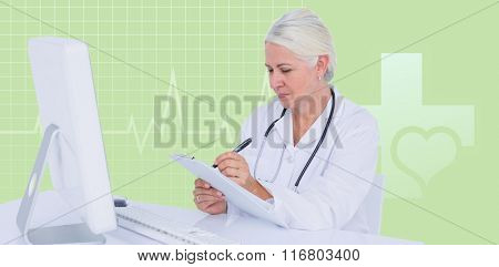 Female doctor writing on clipboard while sitting at desk against green background