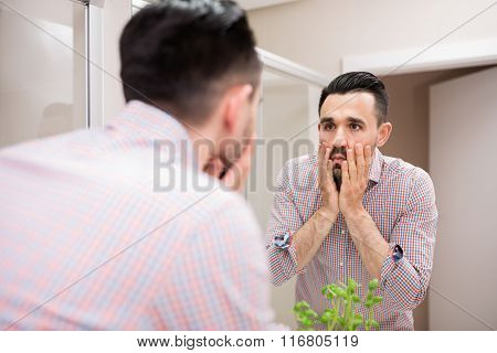 Tired Man Checking His Face In Mirror