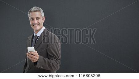 Portrait of smiling businessman holding mobile phone against grey background