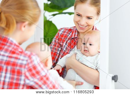 Mother And Baby Look In The Mirror  At Home