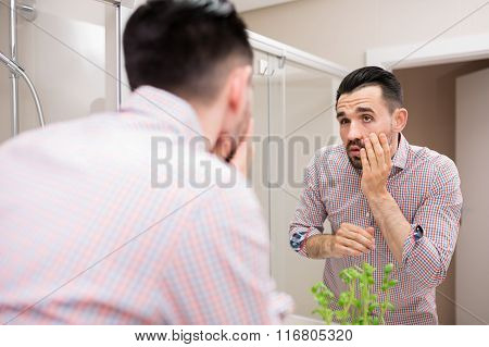 Man In Bathroom Mirror Looking At His Face