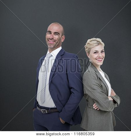 Smiling business people back-to-back against grey background