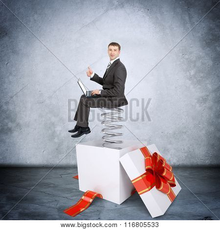 Businessman with laptop sitting on coil spring
