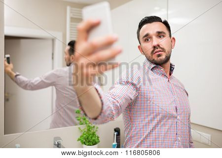 Latin Macho Taking Selfie In Bathroom