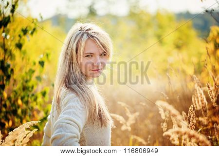 Portrait Young Girl Enjoying The Beauty Of Sunny Autumn Day  In High Grass In An Autumn Park