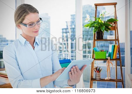 Businesswoman using tablet pc against view of a business desk