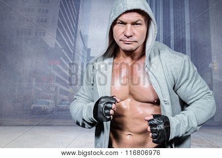 Portrait of confident athlete in hood against urban projection on wall