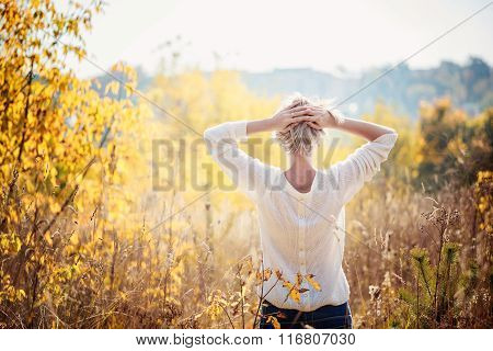 Happy Young Girl Enjoying The Beauty Of Sunny Autumn Day  In High Grass In An Autumn Park. View From