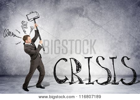 Businessman with hammer and word crisis