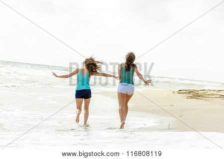 outdoor portrait of two young happy girls running away on tropical sea background, holiday image