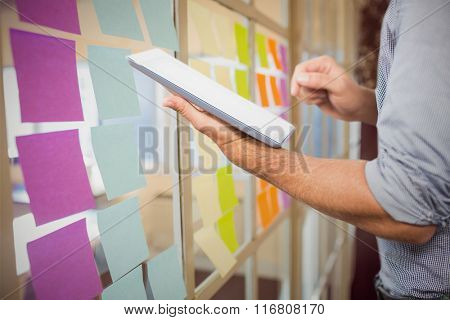 Businessman using digital tablet over white background against colorful adhesive notes
