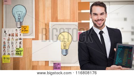 Smiling businessman showing his tablet pc against display of stock figures in detail