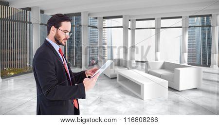 Businessman scrolling on his digital tablet against modern room overlooking city