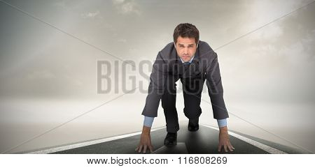 Focused businessman ready to race against misty road landscape