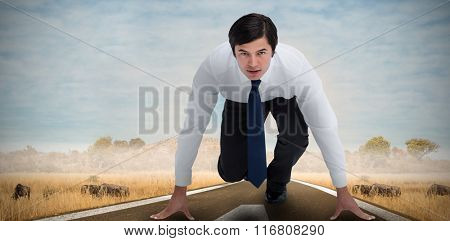 Tradesman in sprinting position against savannah road landscape