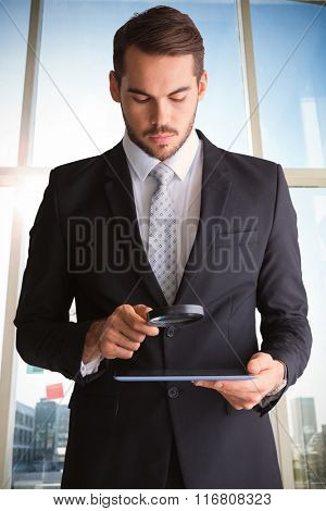Concentrated businessman using magnifying glass against adhesive notes on window