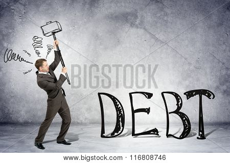 Businessman with hammer and word debt
