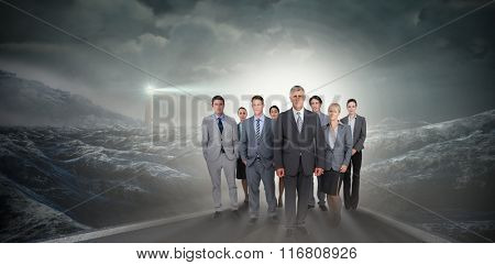 Smiling business team looking at camera against headlight road landscape