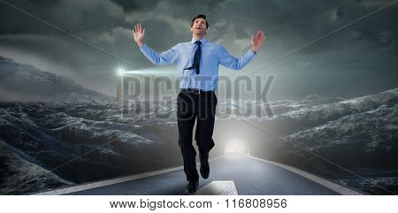 Happy businessman running with hands up against headlight road landscape