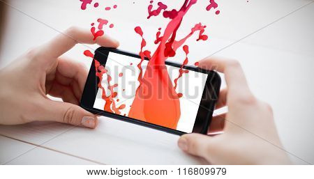 Pink paint splashes and drops against cropped image of man holding smartphone
