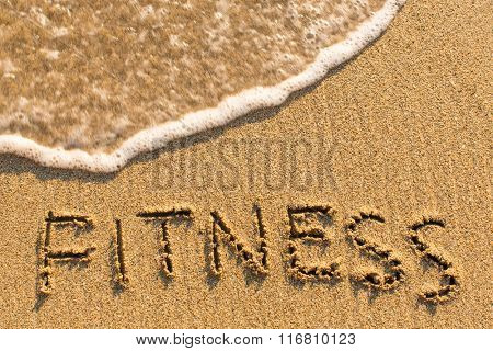 Fitness - word drawn on the sand beach with the soft wave.