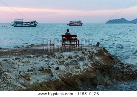 Lonely woman sitting on a bench on a promontory of the sea shore, looking into the distance the sea.
