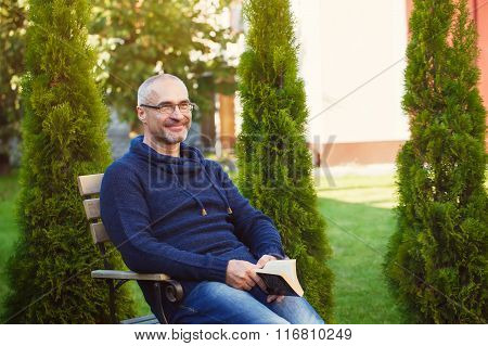 Senior Man Reading Novel In Country Home Garden