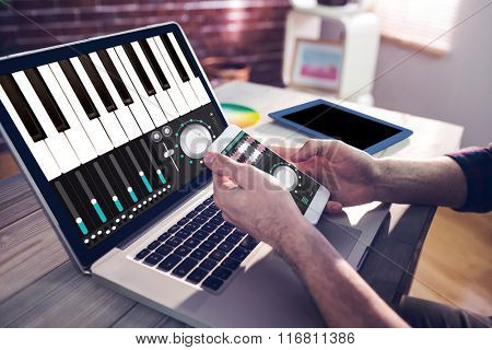 Music app against cropped hand of graphic designer using smartphone and laptop