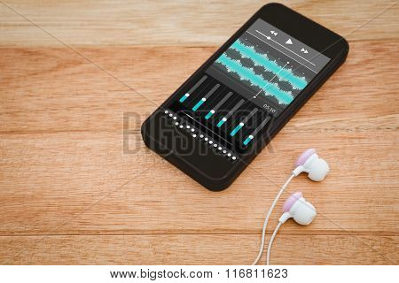 Music app against black smartphone with white headphones