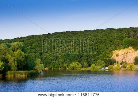 Landscape Of A Hills With Trees, River And Sky