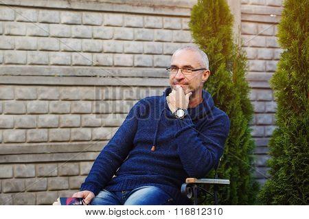 Senior Man Reading Novel In Country Home Garden