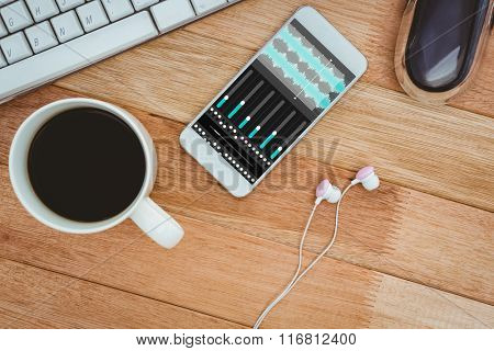 Music app against white smartphone with cup of coffee