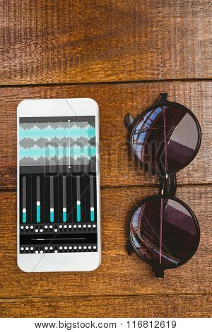 Music app against view of glasses and a smartphone