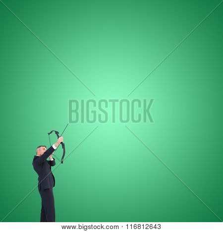 Businessman shooting bow and arrow against green vignette