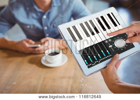 Music app against person using tablet computer in cafe