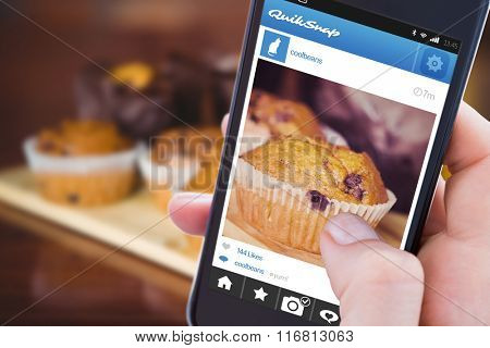 Woman using her mobile phone against chocolate chip muffins on cutting board