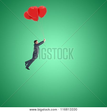 Businessman flying with balloons against green vignette