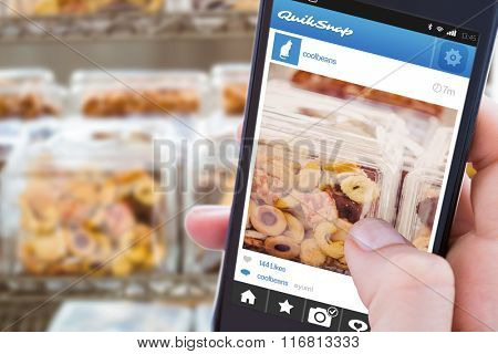 Woman using her mobile phone against close up of jars full of biscuits