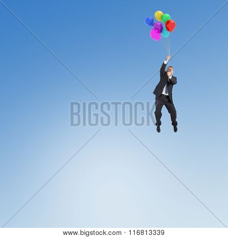 Businessman flying with balloons against blue sky