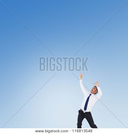 Businessman with hands raised on white background against blue sky