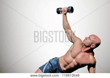 Man exercising with dumbbells against grey vignette