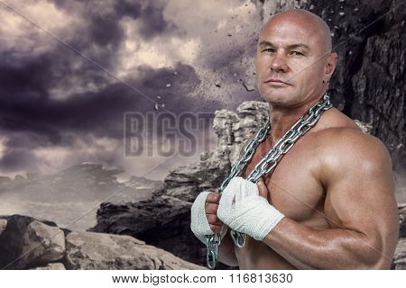Portrait of confident bodybuilder holding chain against rock crashing down from cliff