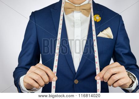 Man In Blue Suit Bowtie, Brooch, Pocket Square Blue Suit Carry Measurement Tape