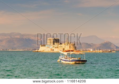 Old fishing boat against the Bourtzi castle at Nafplio in Greece.