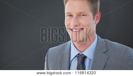 Smiling businessman looking at camera against grey background