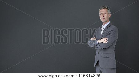 Businessman standing arms crossed over white background against grey background