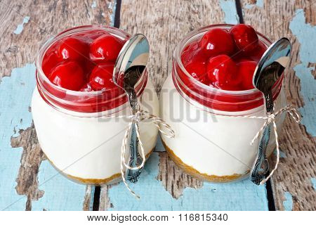 Two cherry cheesecakes in mason jars on a rustic wood